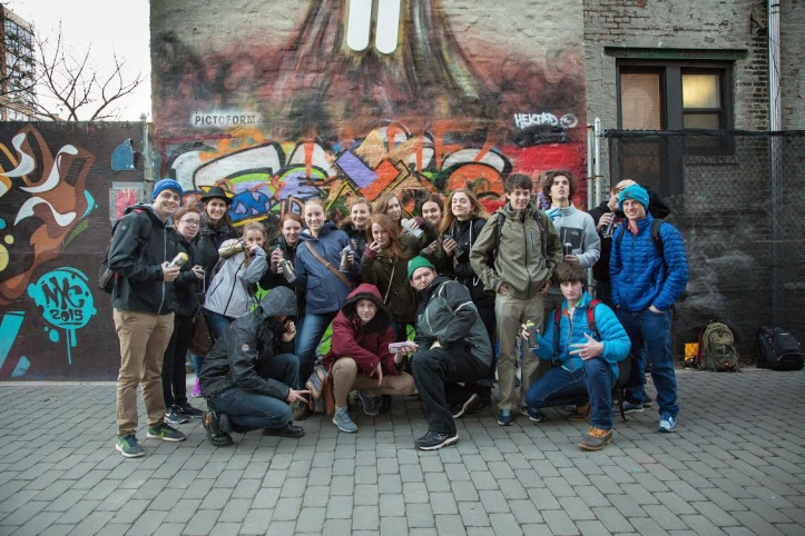 The student group posing with graffiti artists